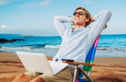 Мужчина с ноутбуком у моря